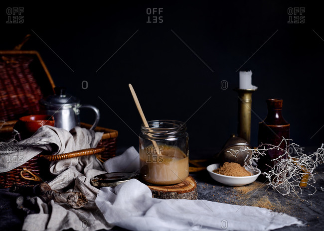 Still life of yummy caramel with cane sugar powder as ingredient placed on table in arrangement with tea set in wicker basket and various decor elements against blurred dark background in studio