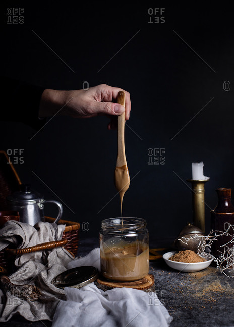 Unrecognizable female cook holding teaspoon over transparent glass jar of tasty caramel placed on table in arrangement with tea set in wicker basket and various decor elements against blurred dark background in studio