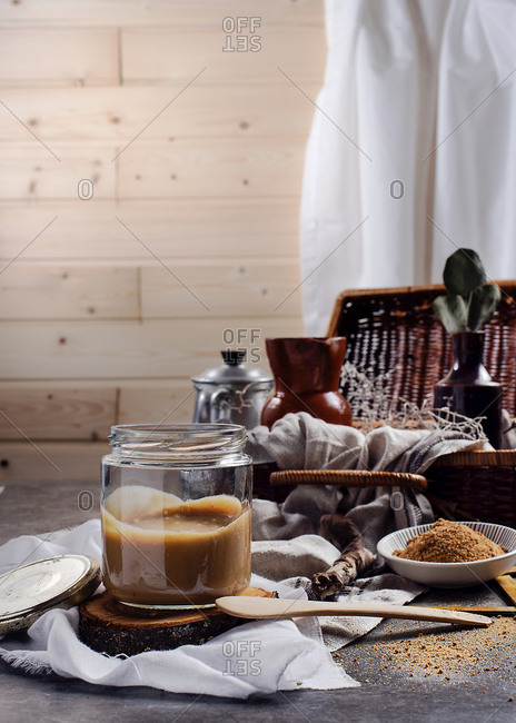 Transparent glass jar of tasty caramel placed on wooden stand among white fabric on table beside bowl with cane sugar powder at home