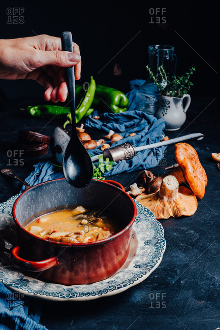 Cropped hand of unrecognizable person holding a spoon near a bowl with delicious soup placed on table with red pine mushrooms and spicy green chili pepper served for dinner