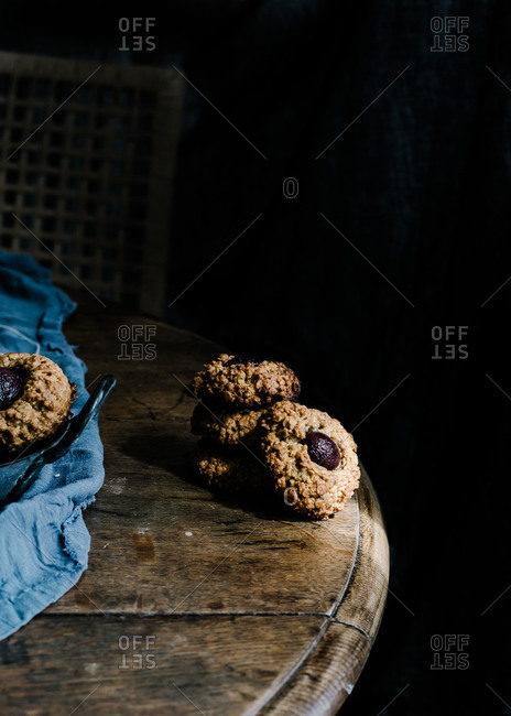 From above of yummy baked cherry cookies placed on wooden table with piece of cloth and vintage iron