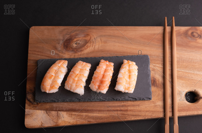 Top view of delicious sushi with rice and shrimps served on wooden board with chopsticks in restaurant