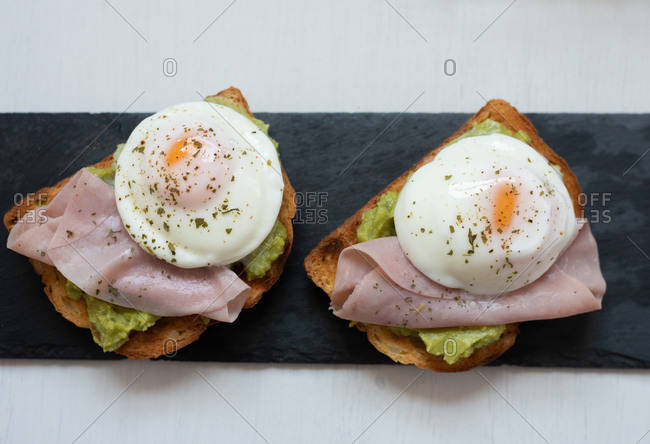 From above of appetizing toasts with guacamole garnished with tasty fried eggs and ham placed on table for breakfast
