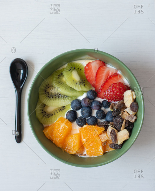 From above of delicious healthy breakfast with sliced kiwi and oranges placed in bowl with blueberries and strawberries