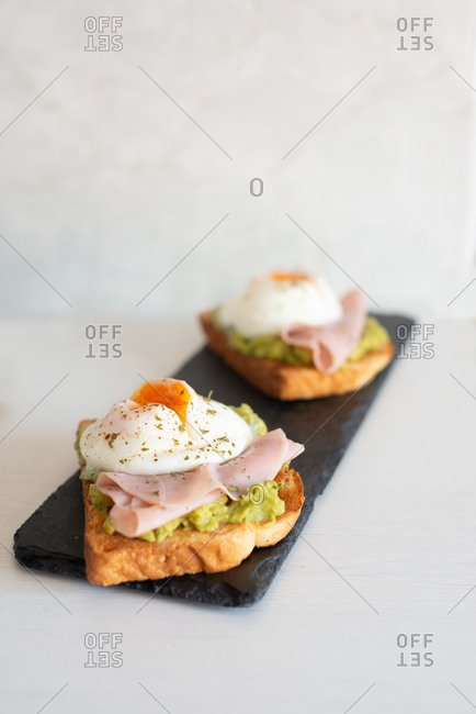 Tasty breakfast from crispy toasts garnished with guacamole and fried eggs with ham in bright kitchen