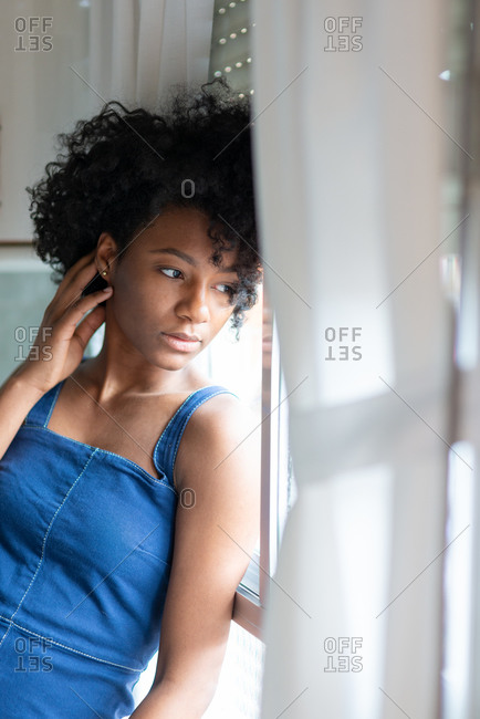 Side view of thoughtful exhausted black housewife with afro hairstyle sitting on counter and relaxing during housework while looking away near windows