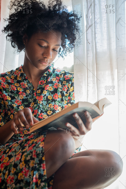 Calm thoughtful ethnic female in stylish dress with floral print sitting in armchair reading a book at home