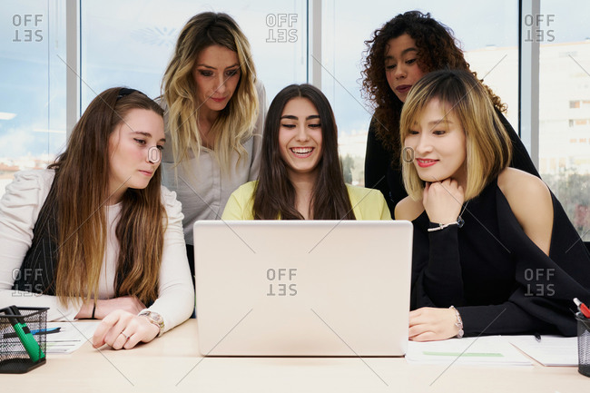 Group of focused young multiracial female colleagues in casual clothes gathering around laptop and watching business information while working together in modern workspace