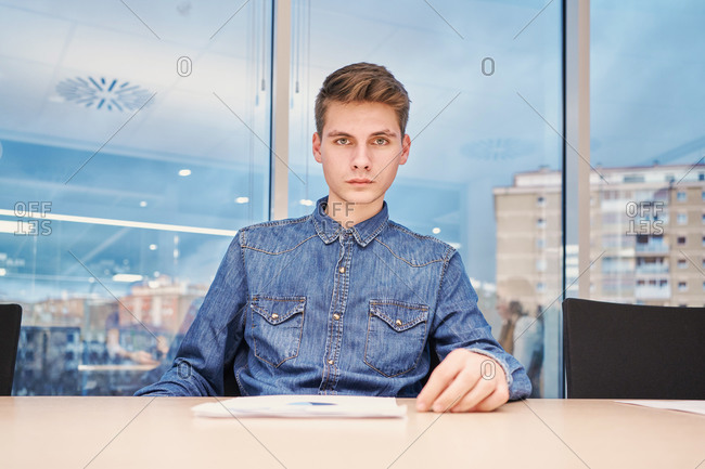 Serious male worker in casual shirt sitting at table in modern open space workplace and reading documents