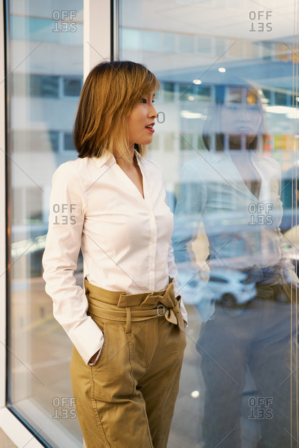 Determined female entrepreneur in classy clothes standing near window in modern coworking space and looking at camera