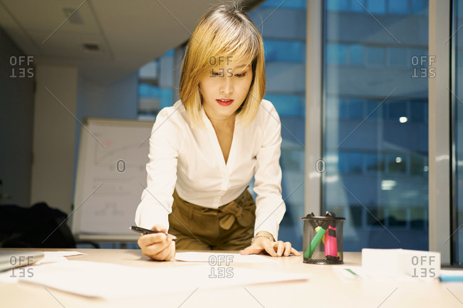 Low angle of smiling Asian businesswoman in elegant wear standing near table and reading paper reports while working in contemporary office