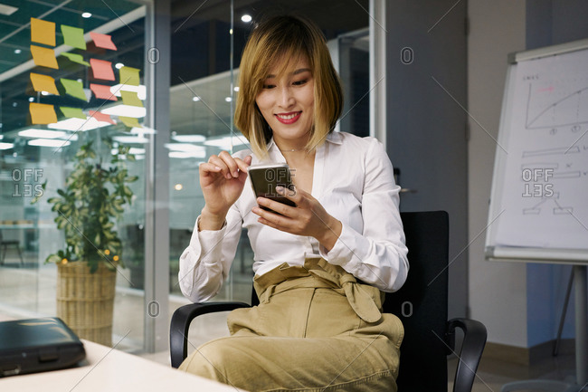 Female entrepreneur in elegant outfit sitting in office chair and using smartphone in modern workspace