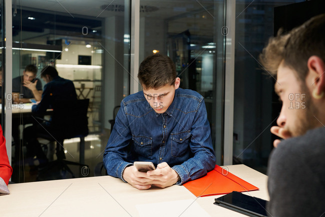 Pensive male employee in casual wear sitting at table with diverse coworkers during business meeting and browsing mobile phone