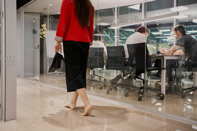 Back view of well dressed executive female with high heels in hand walking along corridor of modern workplace