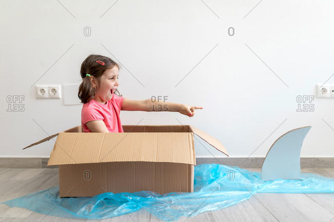Playful preteen kid sitting in carton box at home and pretending to be sailor with paddle in boat screaming and pointing with finger on shark swimming beside