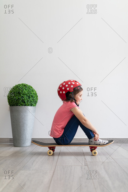 Side view of little kid in red spotted helmet and casual clothes and dreaming about outdoors amusement while sitting alone on longboard and embracing knees in corridor of light modern apartment staying at home