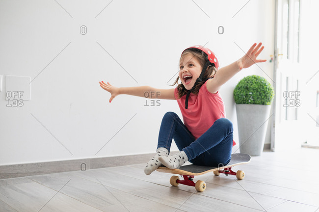 Little kid in red spotted helmet and casual clothes and dreaming about outdoors amusement while sitting alone on longboard in corridor of light modern apartment staying at home