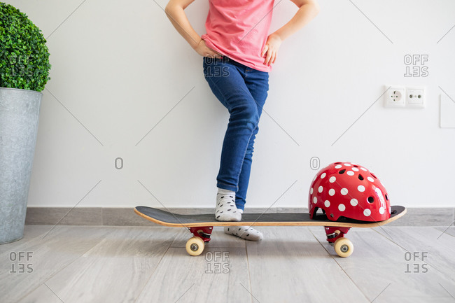 Low angle of faceless cool preteen kid in casual clothes with longboard and vivid red protective helmet in light contemporary flat dreaming about street staying at home