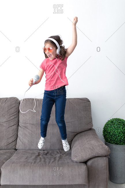Cheerful small child in pink glasses and headphones looking away and jumping on sofa while having fun using microphone and pretending artist in light living room of contemporary flat