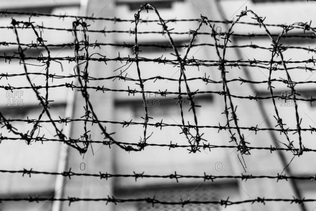 Black and white of spiky barbed wire above fence of local place of criminal confinement in Hong Kong