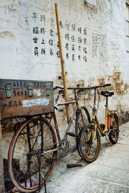 - June 2, 2020: Pair of shabby bikes leaned on stone wall with drawn hieroglyphs near town temple in Hong Kong