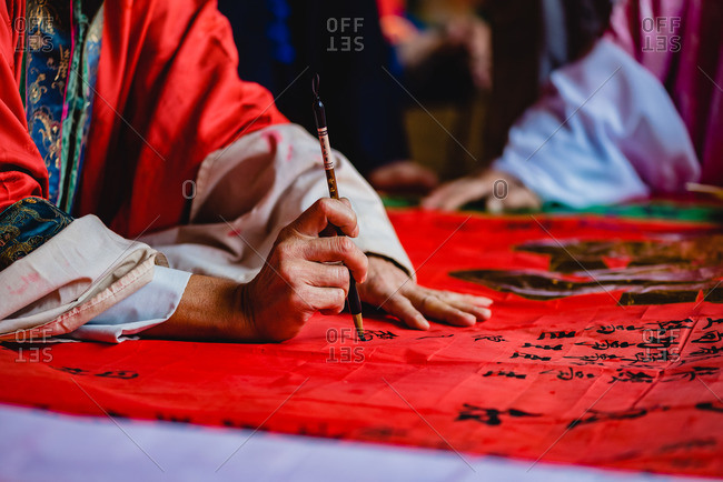 - June 2, 2020: Crop master in kimono painting black hieroglyphs with ink on red textile in temple of Hong Kong