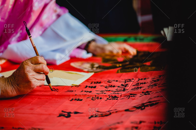- June 12, 2020: Crop master in kimono painting black hieroglyphs with ink on red textile in temple of Hong Kong