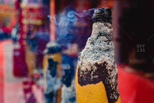 Yellow colored big incense stick smoking slightly outside of temple in Hong Kong