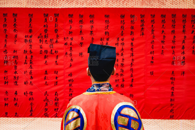 - June 2, 2020: Back view of anonymous person wearing colorful Chinese clothing looking at red fabric with drawn hieroglyphs