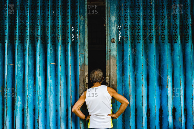 Back view of aged man in tank top holding arms on waist while looking inside of blue doorway in Hong Kong