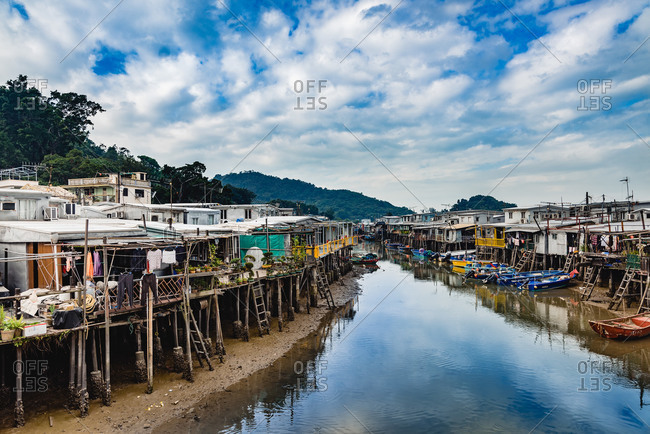 - June 2, 2020: Perspective view of peaceful city river with small houses and wooden piers on both sides under bright cloudy sky in Hong Kong