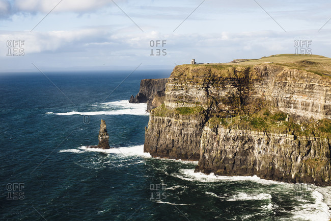 Majestic view of rough and high cliffs on seashore of Ireland with ocean waves crashing against