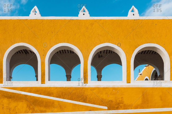 Exterior of vivid yellow walls with arches in ancient city of Izamal against blue sky