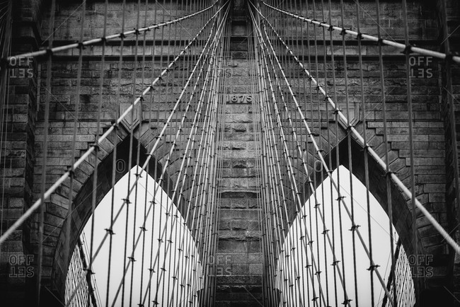 Low angle of stone towers with pointed arches of suspension Brooklyn bridge on cloudy day