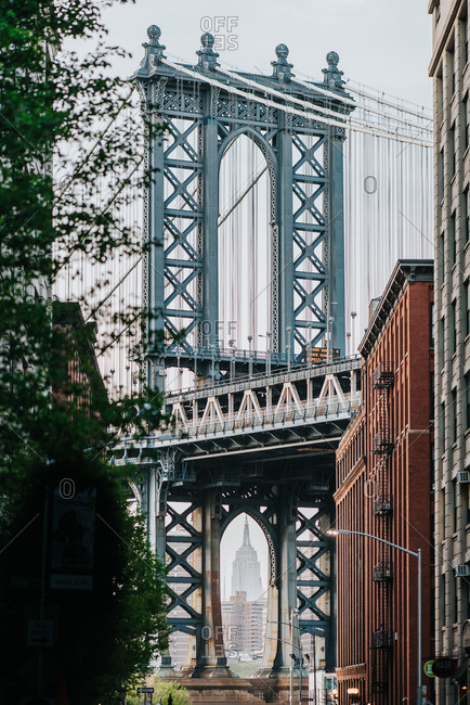 - June 12, 2020: Scenic view of Manhattan Bridge in New York City through leafy tree branches in misty day
