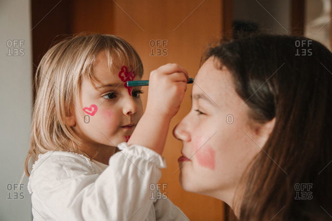 Side view of little girl painting face of teen sister while having fun at home