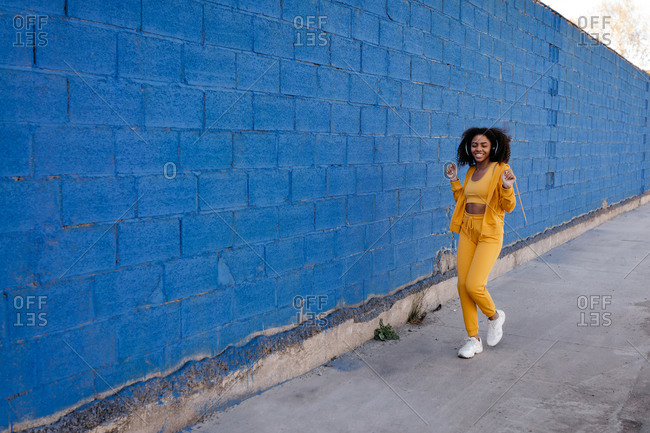 Satisfied African American female in bright clothes dancing with closed eyes near blue brick wall and enjoying songs in wireless headphones