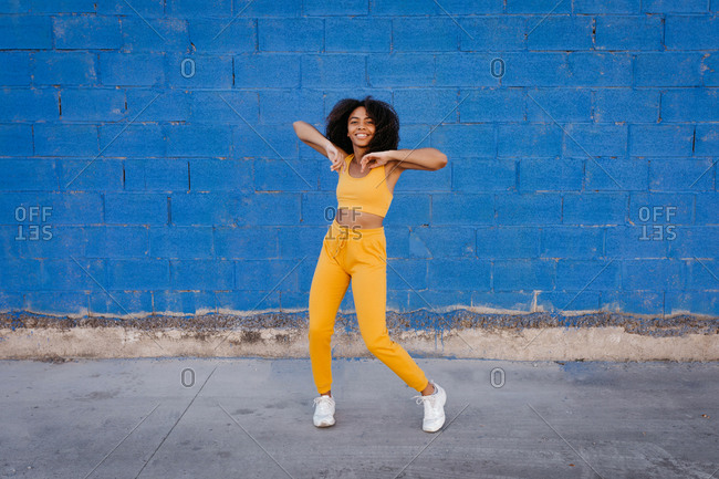 Delighted ethnic female in yellow clothes in moment of dancing with arms apart on background of vivid blue wall on street