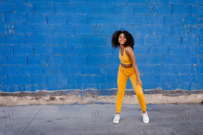 Delighted ethnic female in yellow clothes in moment of dancing on background of vivid blue wall on street