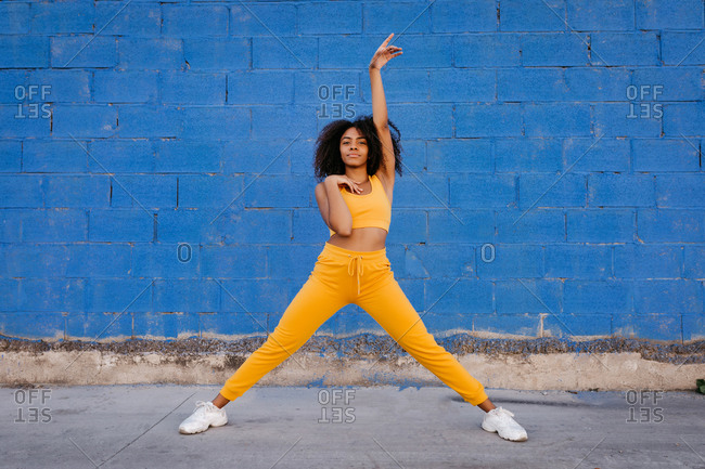 Delighted ethnic female in yellow clothes in moment of dancing with legs apart on background of vivid blue wall on street