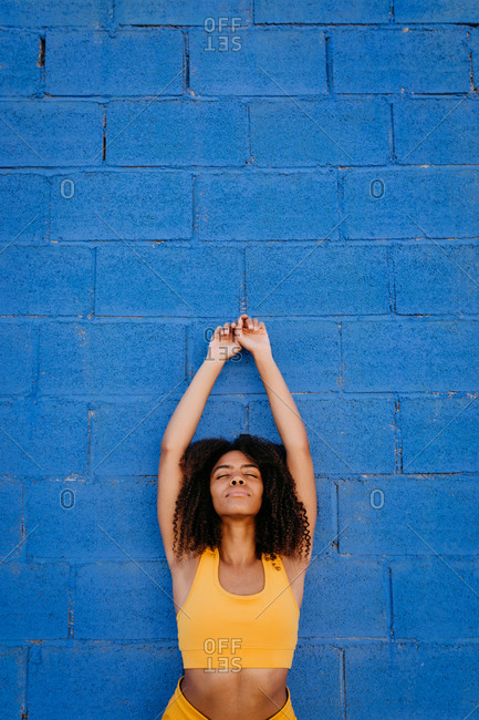 Tranquil black female in yellow outfit and with afro hairstyle standing with raised arms near blue stone wall while daydreaming with closed eyes