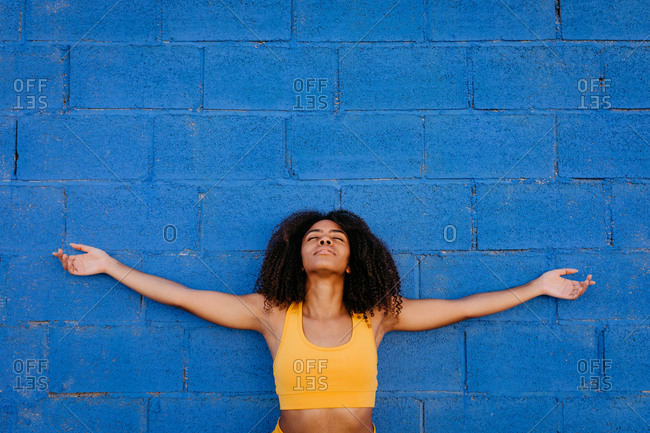Tranquil black female in yellow outfit and with afro hairstyle standing with open arms near blue stone wall while daydreaming with closed eyes