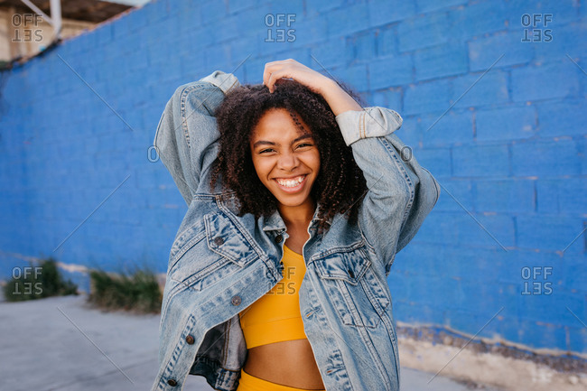 Young black female in denim jacket standing near blue wall in city and showing toothy smile while looking at camera