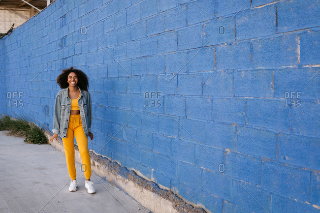 Young black female in denim jacket standing near blue wall in city and showing toothy smile with closed eyes