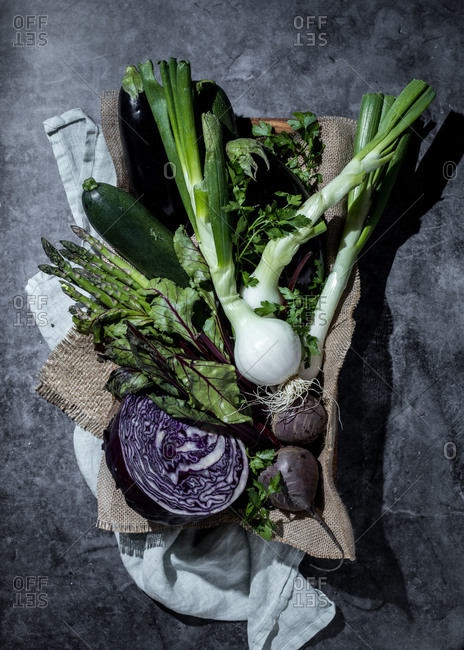 Top view of purple cabbage and beets in composition with cucumber and aubergine among fresh green herbs on natural fabrics on gray table in garden