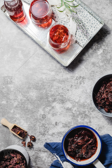 Top view composition with fresh natural hibiscus tea served in glasses on tray placed near bowls with dried flowers on marble table