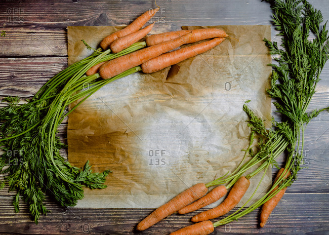 Top view of fresh carrots on wooden table with blank space for text