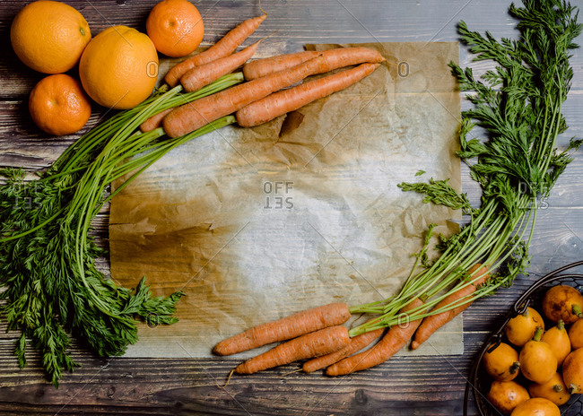 Top view of various orange fruits arranged with bunches of fresh carrots on wooden table with blank space for text