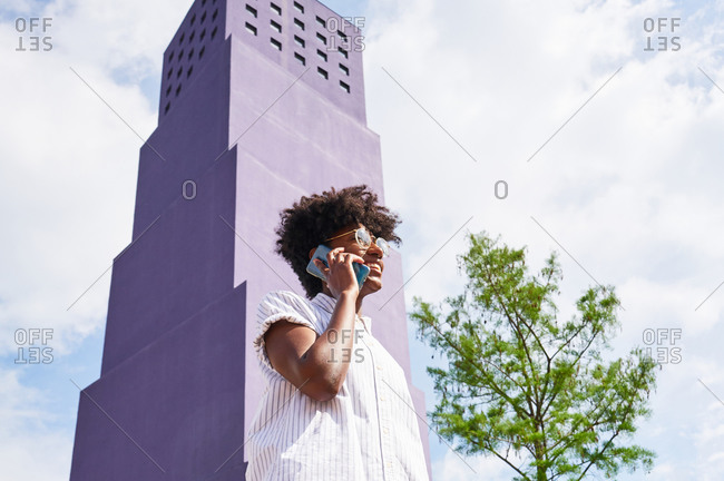 From below side view of slender African American female in white dress and boots looking away and talking on phone while standing alone against multistory violet building in city in sunny summer day