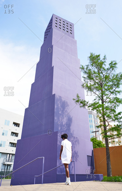 From behind view of slender African American woman in white dress and boots walking alone against multistory violet building in city in sunny summer day